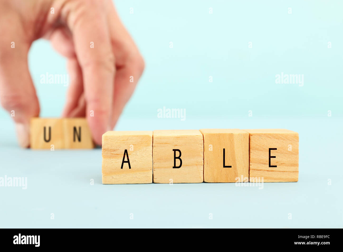 man hand spelling the text unable with wooden cubes, taking out the word un so it written able. success and challenge concept - Stock Image