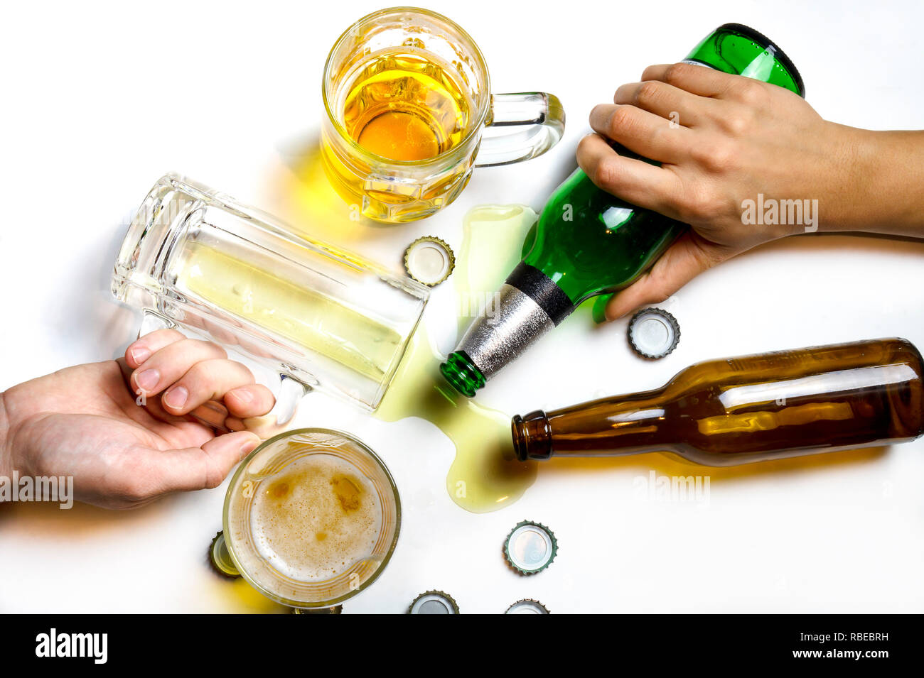 When the party is over oncept. Hands of people passed out on messy table after beer party Stock Photo