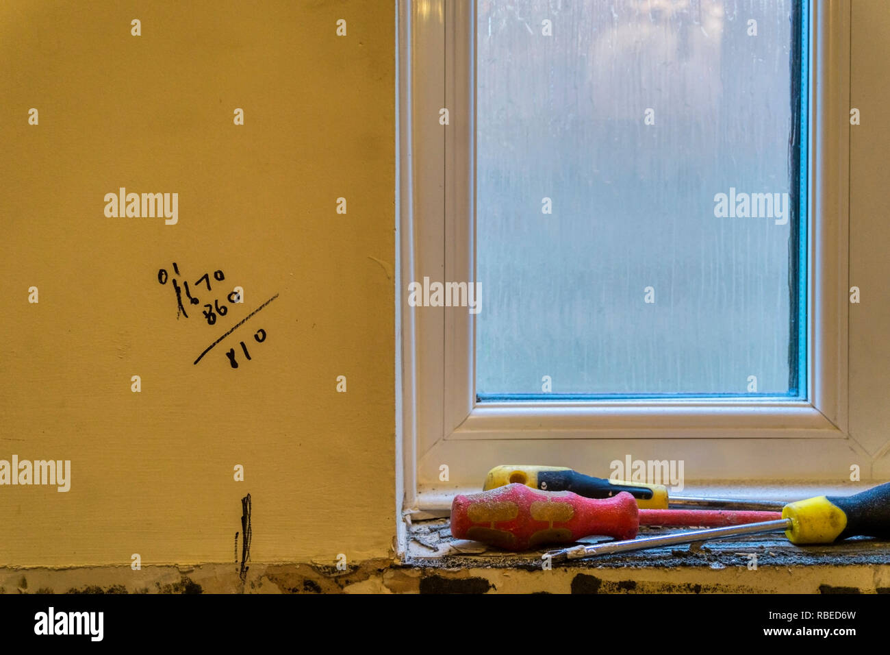 Builders calculations written on wall while building work is carried out. - Stock Image