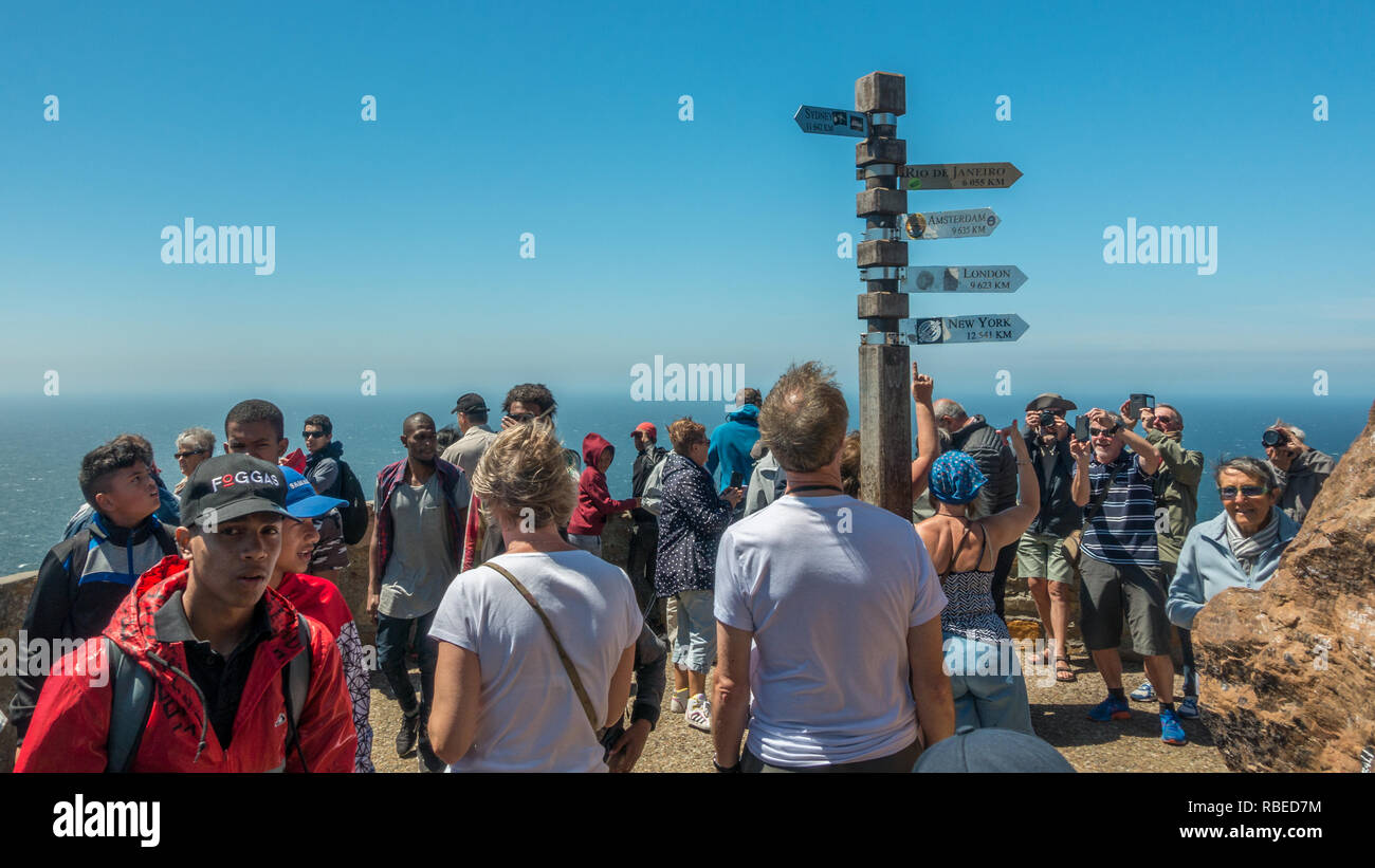 Tourists taking photos of themselves of an international signpost at Cape Point, South Africa. - Stock Image