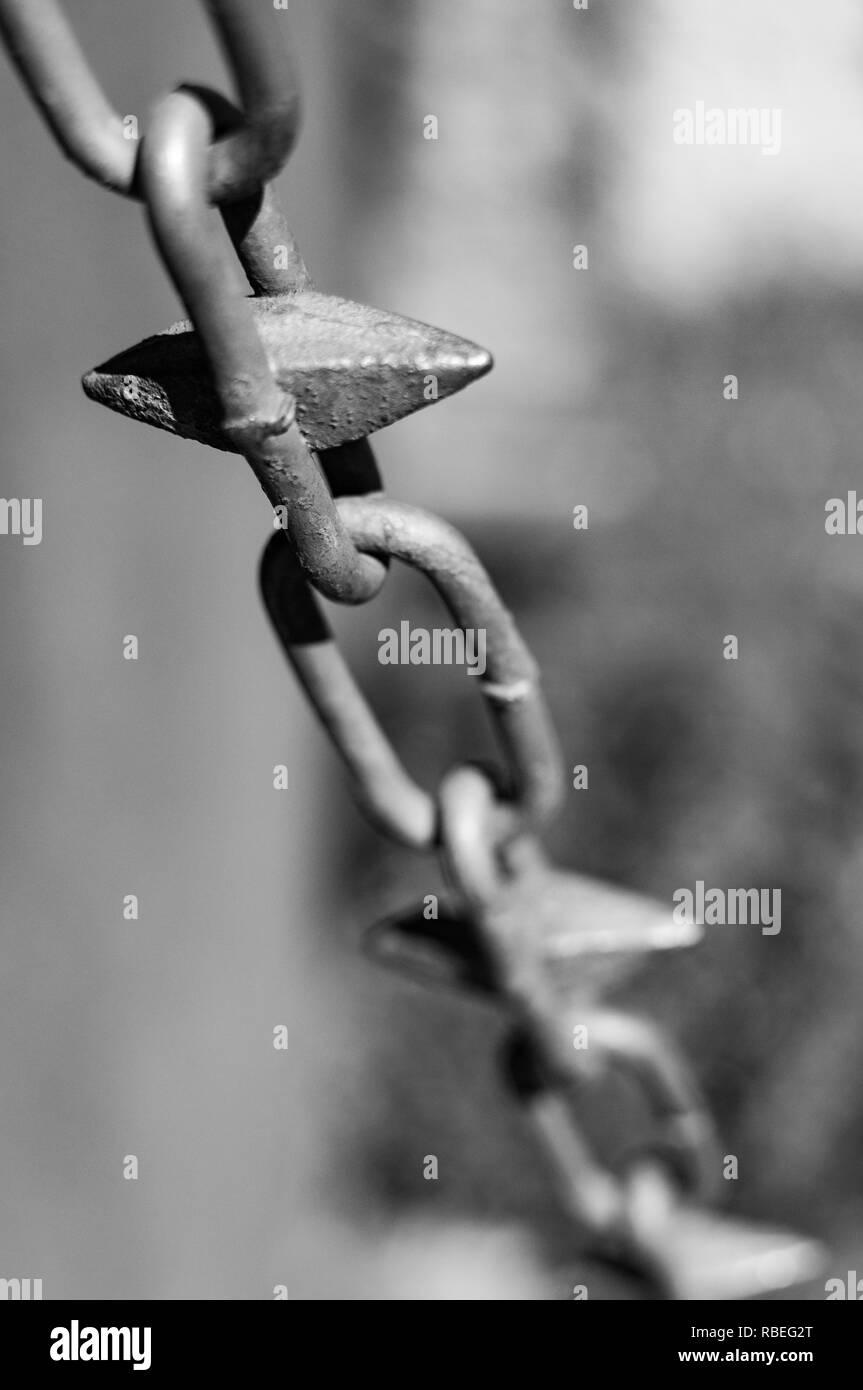 A black and white image of a close up of a metal chain fence. - Stock Image