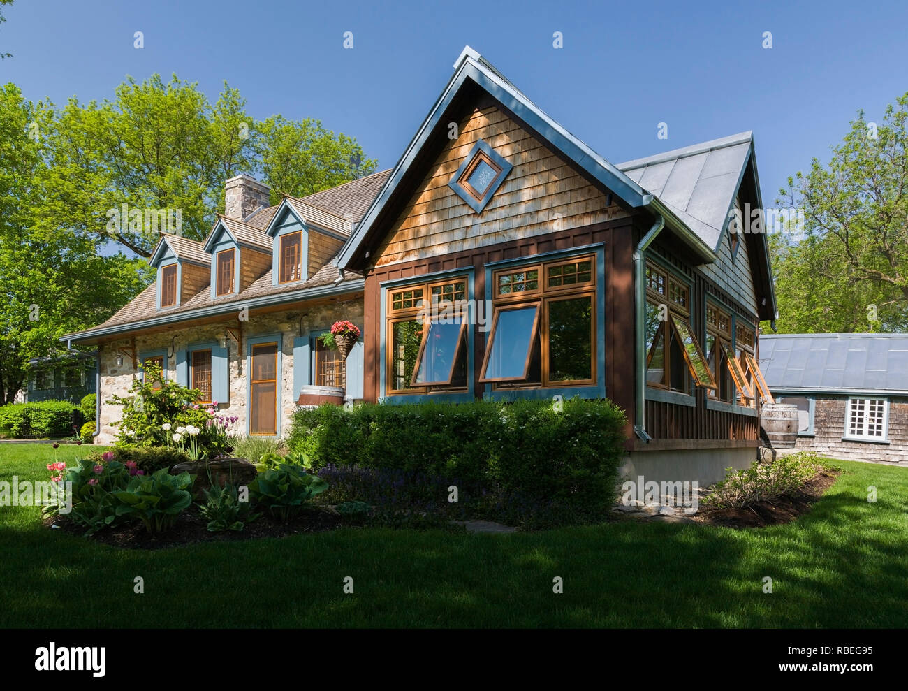 Old circa 1740 Canadiana fieldstone cottage style home facade with new extension in spring - Stock Image