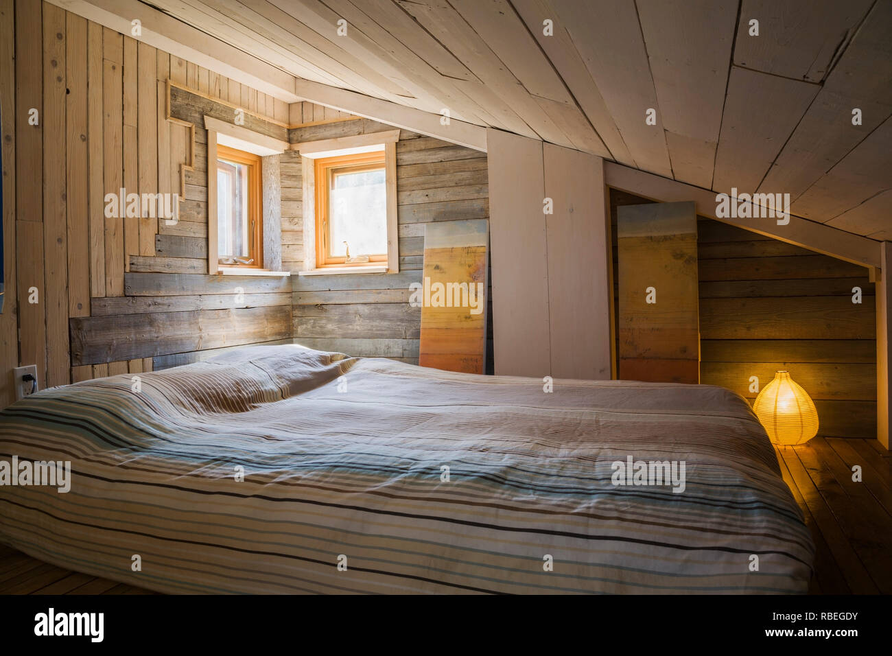 Mezzanine bedroom with old barn wood walls, sloped ceiling and queen ...