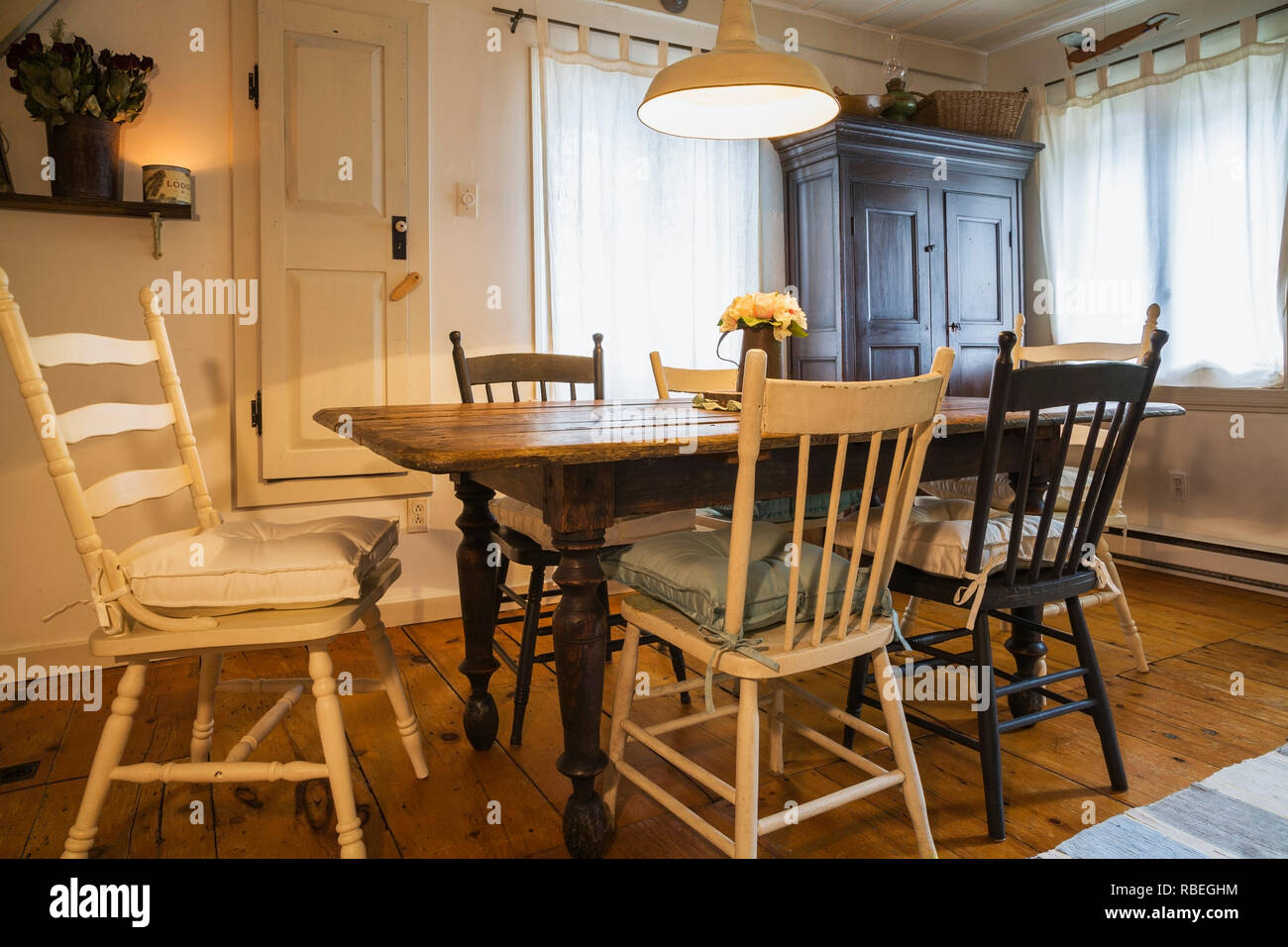 Antique wooden dining table with assorted coloured chairs ...