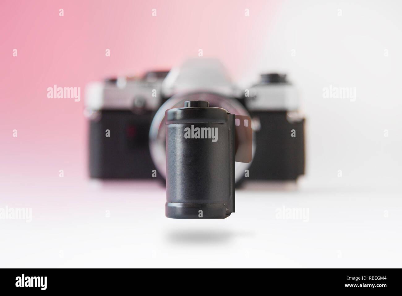 Soaring 35 mm Negative Film Canister on Blurry SLR Camera Back - Stock Image