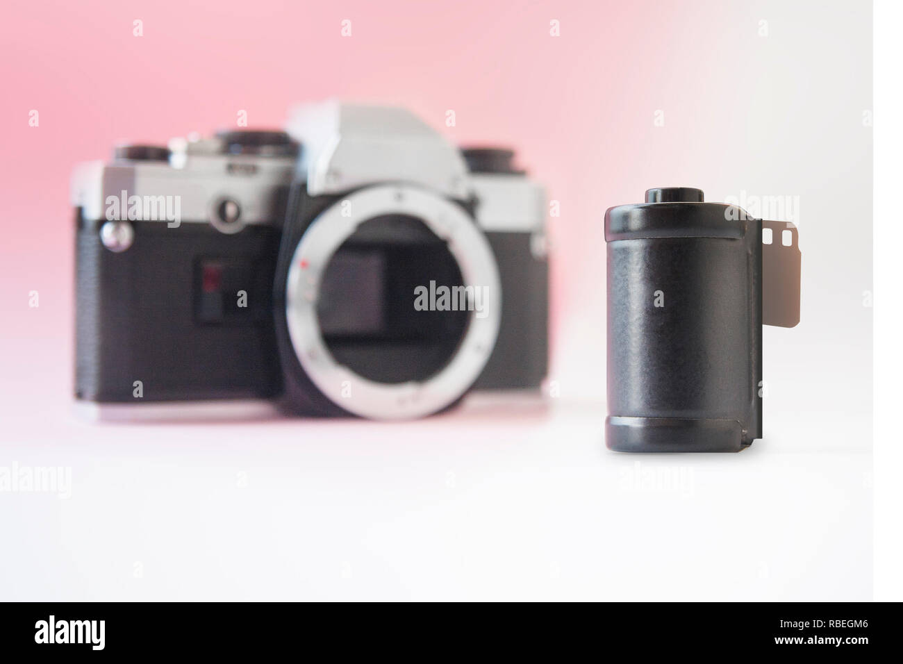 35 mm Film Canister on Blurry SLR Camera Back - Stock Image