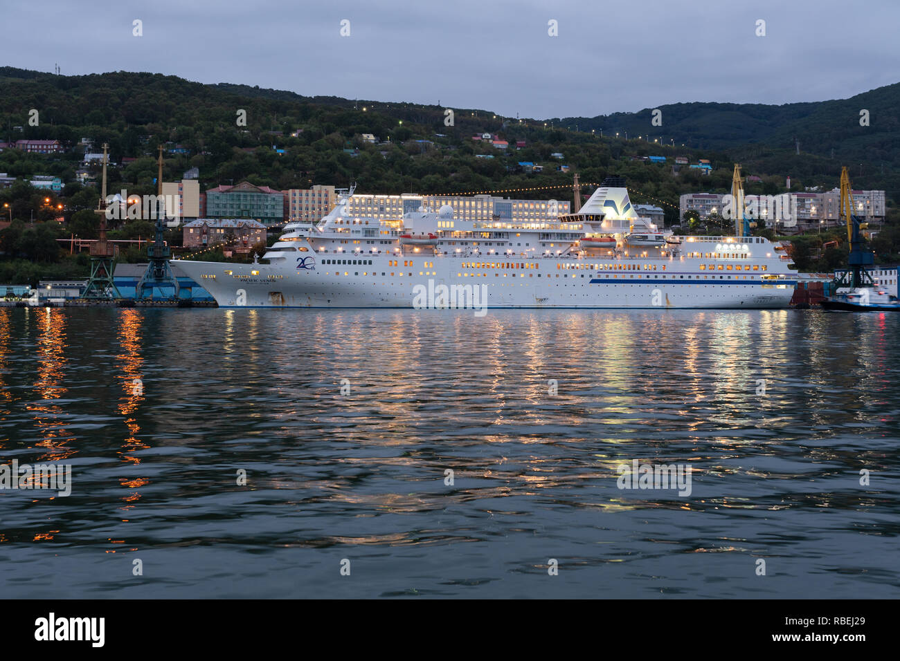 Picturesque night view of white Japanese cruise liner Pacific Venus anchored at pier in Petropavlovsk-Kamchatsky Seaport - Stock Image