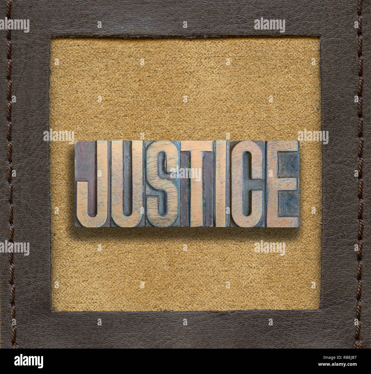 justice word assembled from vintage wooden letterpress inside stitched leather frame - Stock Image