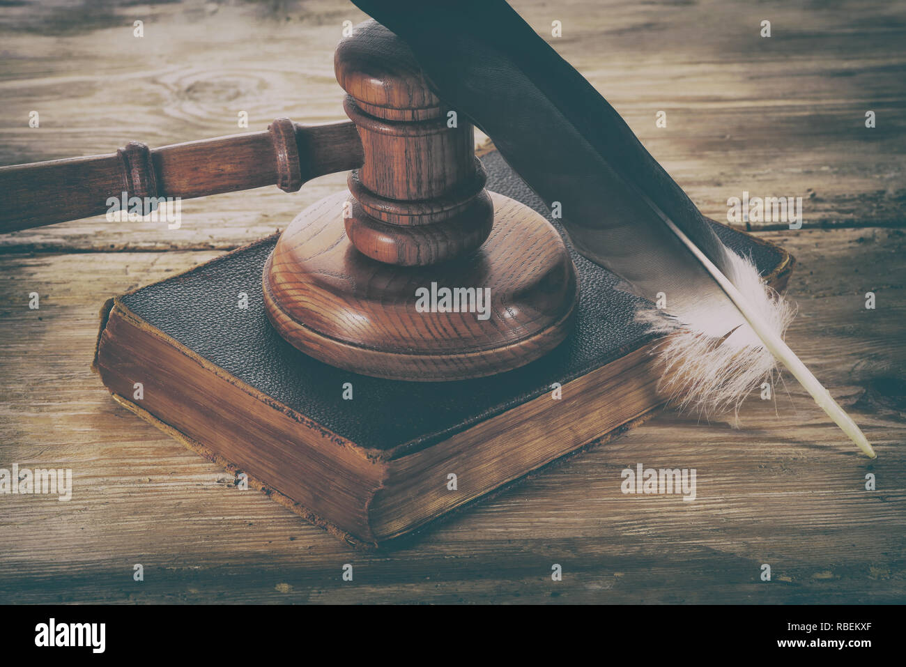 Law gavel or judge mallet and feather pen on a wooden desk Stock Photo