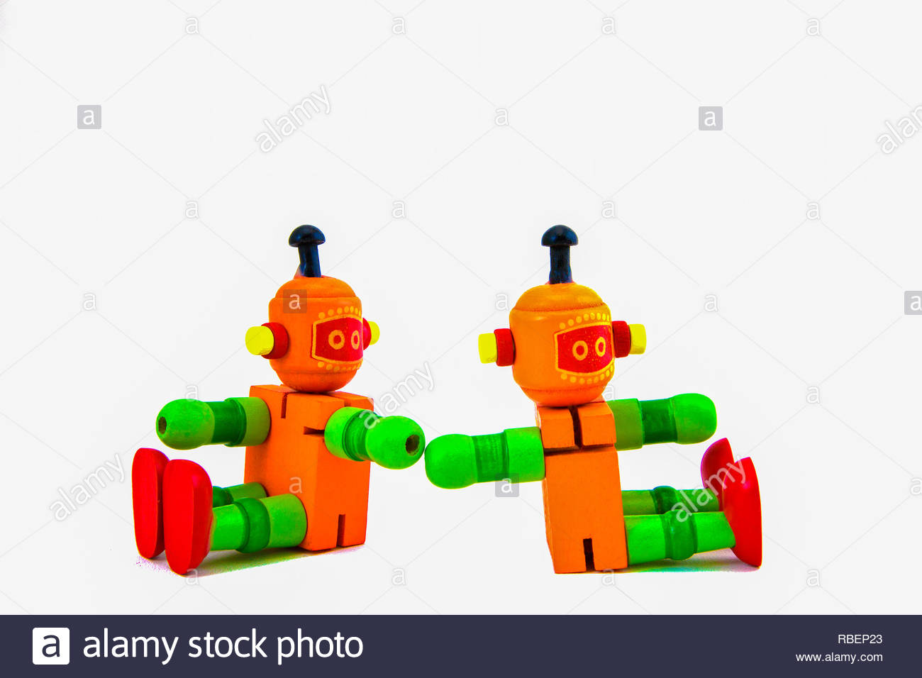 Studio shot of two sitting orange and green wooden toy robots facing away from each other but reaching out. Copy space on a white background. - Stock Image