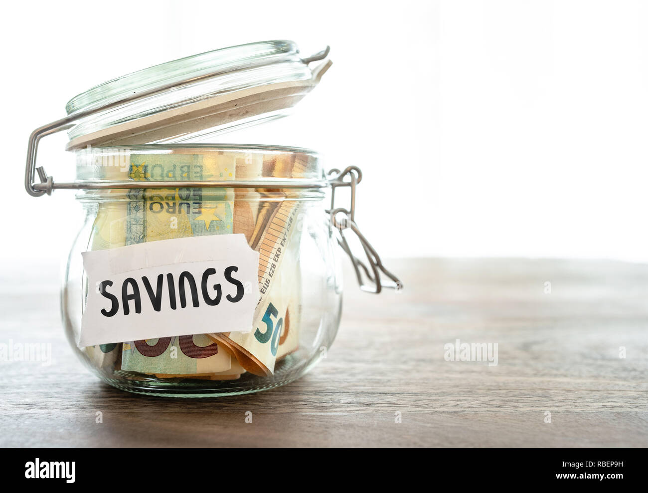 paper money in jar on wooden table Stock Photo
