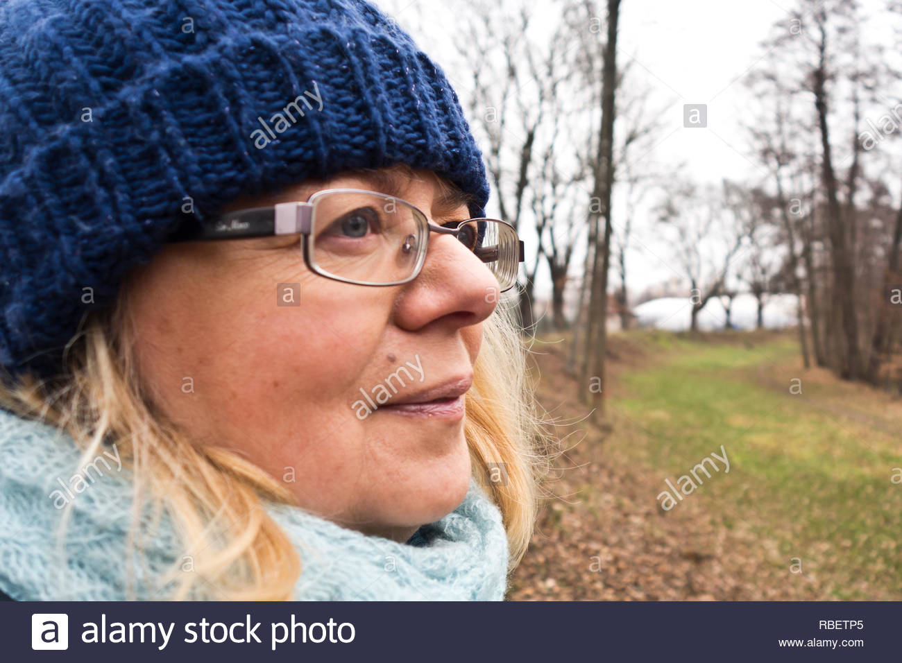 woman in her fifty looking ahead in a winter nature landscape - Stock Image