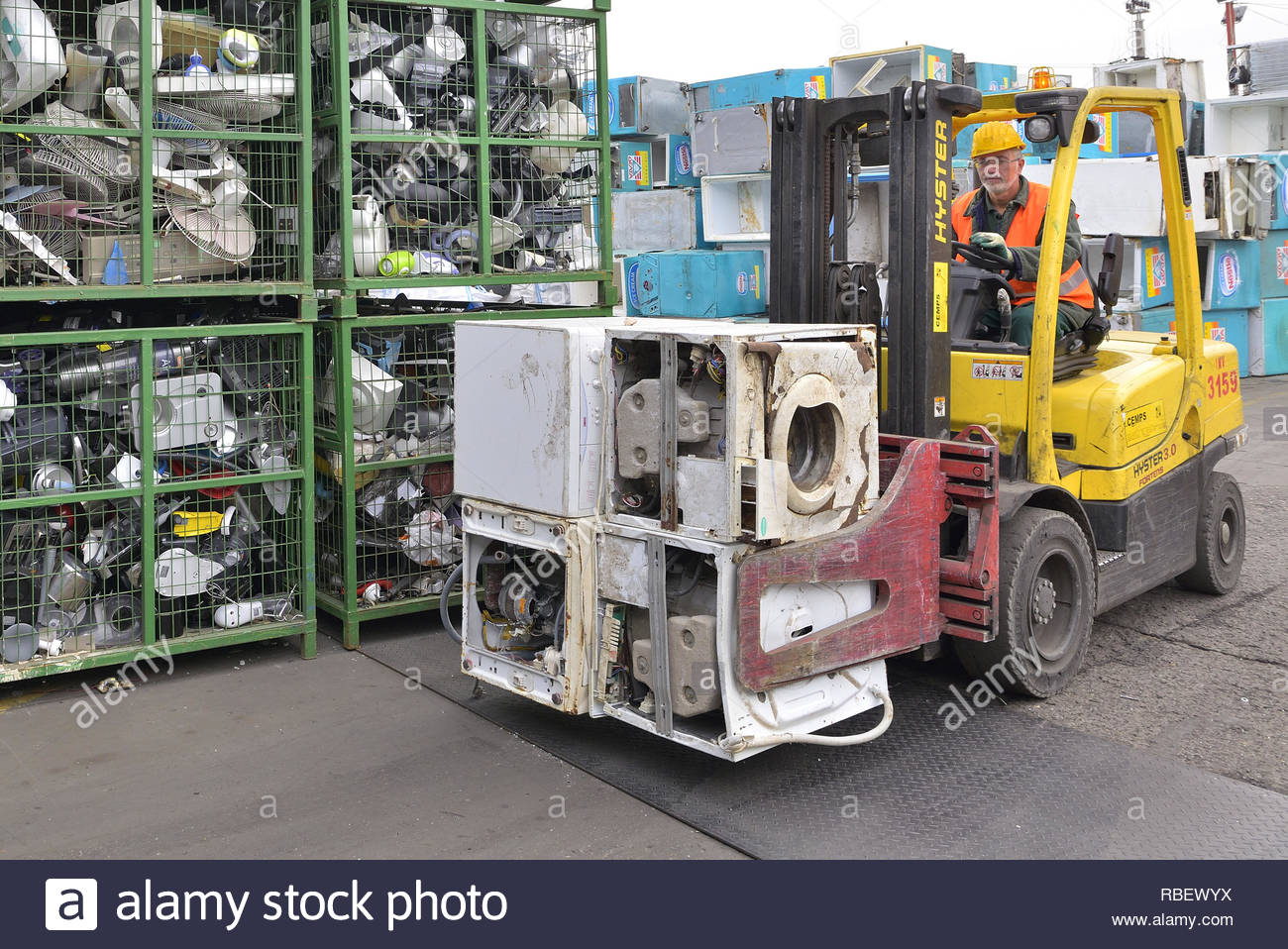 Bucharest, Romania - October 2013: Worker moving electronic waste from a container with segregated electronic devices, ready to be recycled on a recyc - Stock Image