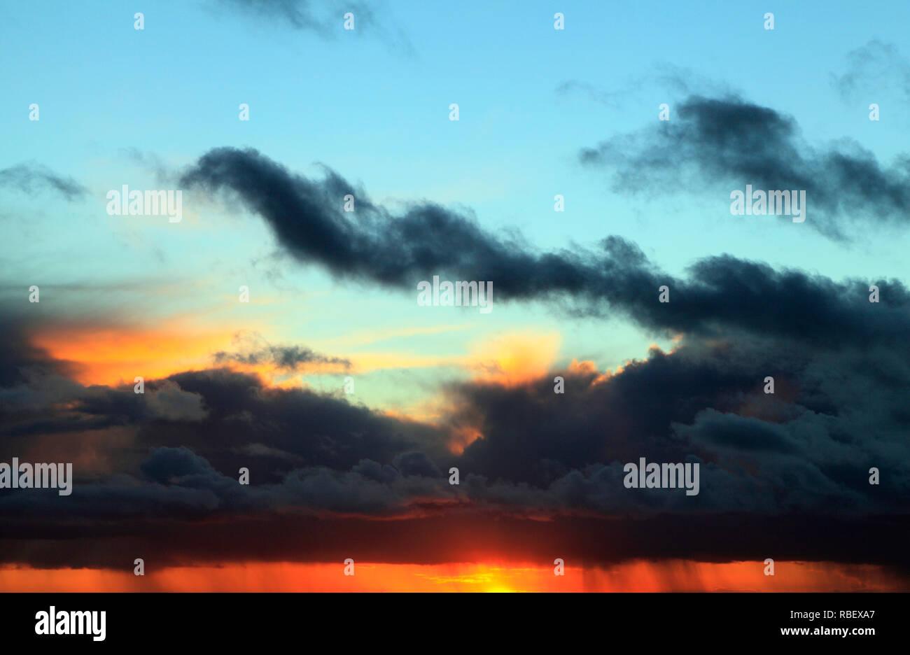 Sunset, red, blue, pink, sky, black clouds, gathering storm, weather, skies, sky, formation, formations, evening light, Norfolk, England, UK - Stock Image