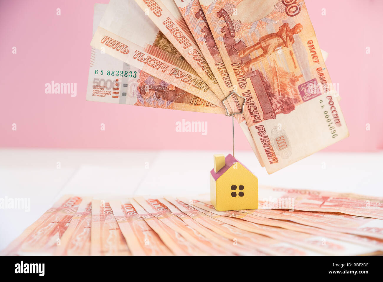 Mortgage loading real estate property with loan money bank concept.money and miniature house model isolated on pink background.Business, finance,saving money,banking ,house loan or insurance concept.russian money. - Stock Image