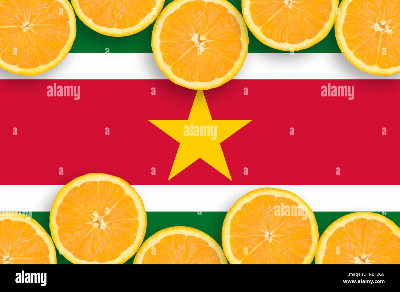 Suriname flag  in horizontal frame of orange citrus fruit slices. Concept of growing as well as import and export of citrus fruits - Stock Image