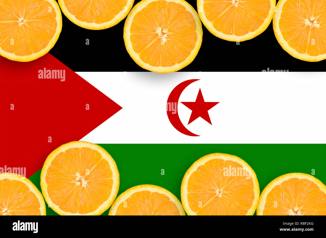 Western Sahara flag  in horizontal frame of orange citrus fruit slices. Concept of growing as well as import and export of citrus fruits - Stock Image