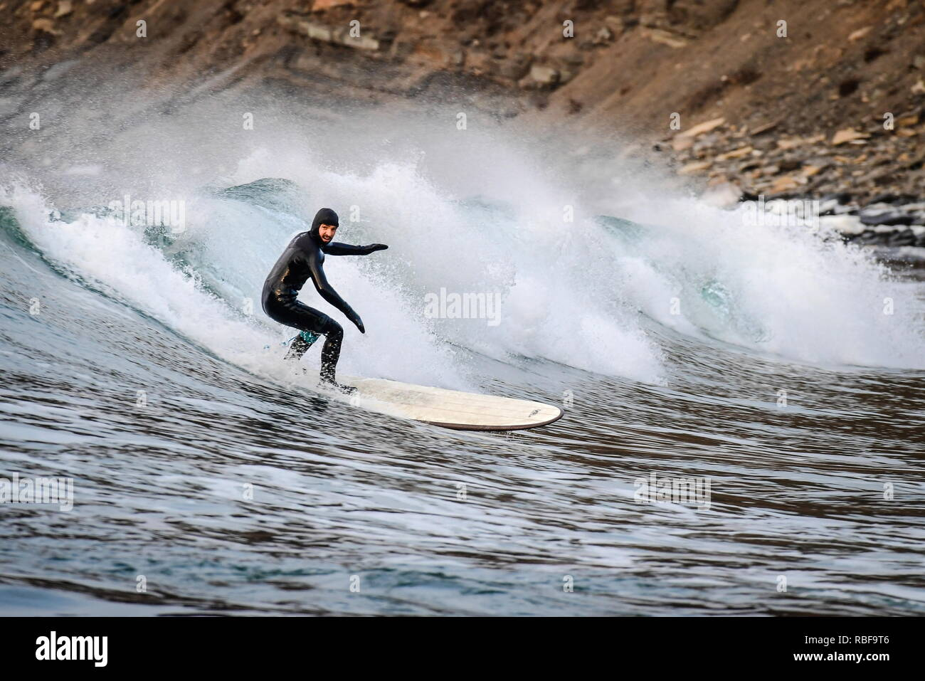 Vladivostok, Russia. 10th Jan, 2019. VLADIVOSTOK, RUSSIA - JANUARY 10, 2019: A man riding a wave in the Ussuri Bay by Russky Island. Yuri Smityuk/TASS Credit: ITAR-TASS News Agency/Alamy Live News - Stock Image