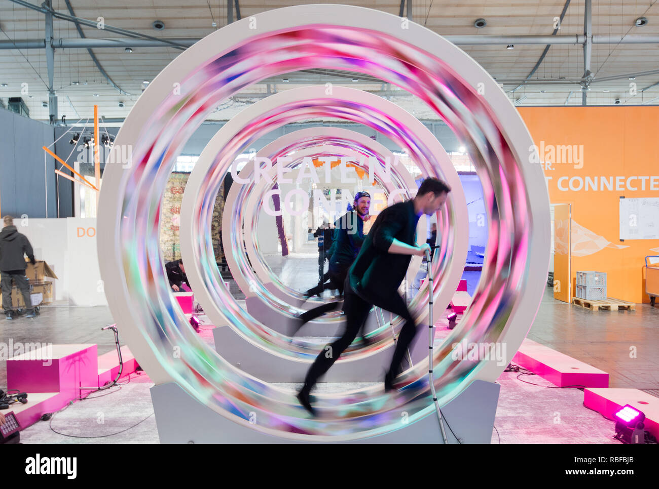 Hannover, Germany. 10th Jan, 2019. Two men run in wheels of the Schmidhuber agency with coloured carpets at the Domotex in the Hanover trade fair. The world's leading trade fair for carpets and floor coverings will take place from 11 to 14 January in Hanover. Credit: Julian Stratenschulte/dpa/Alamy Live News - Stock Image
