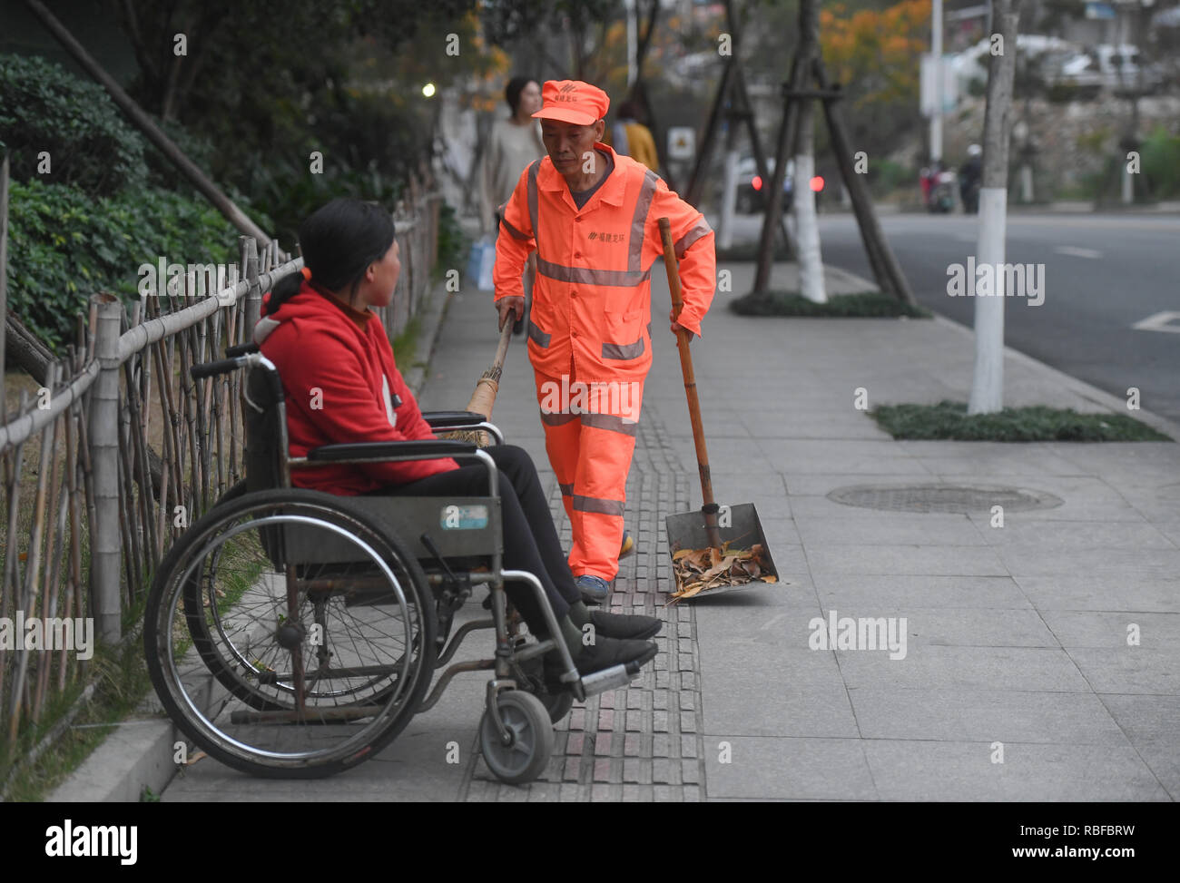 (190110) -- LONGYAN, Jan. 10, 2019 (Xinhua) -- Sanitation worker Dong Jidong cleans the streets accompanied by his handicapped wife Dong Jinxiang in Xinluo District of Longyan City, southeast China's Fujian Province, Jan. 8, 2019. Due to femoral head necrosis disease, Dong Jinxiang has been living on a wheelchair for about a decade. To take care of his handicapped wife, Dong Jidong, who himself has been afflicted with ankylosing spondylitis, gave up his work in a cement plant and chose to clean the streets near their home two years ago just in order to take better care of his wife. Everyday, D - Stock Image