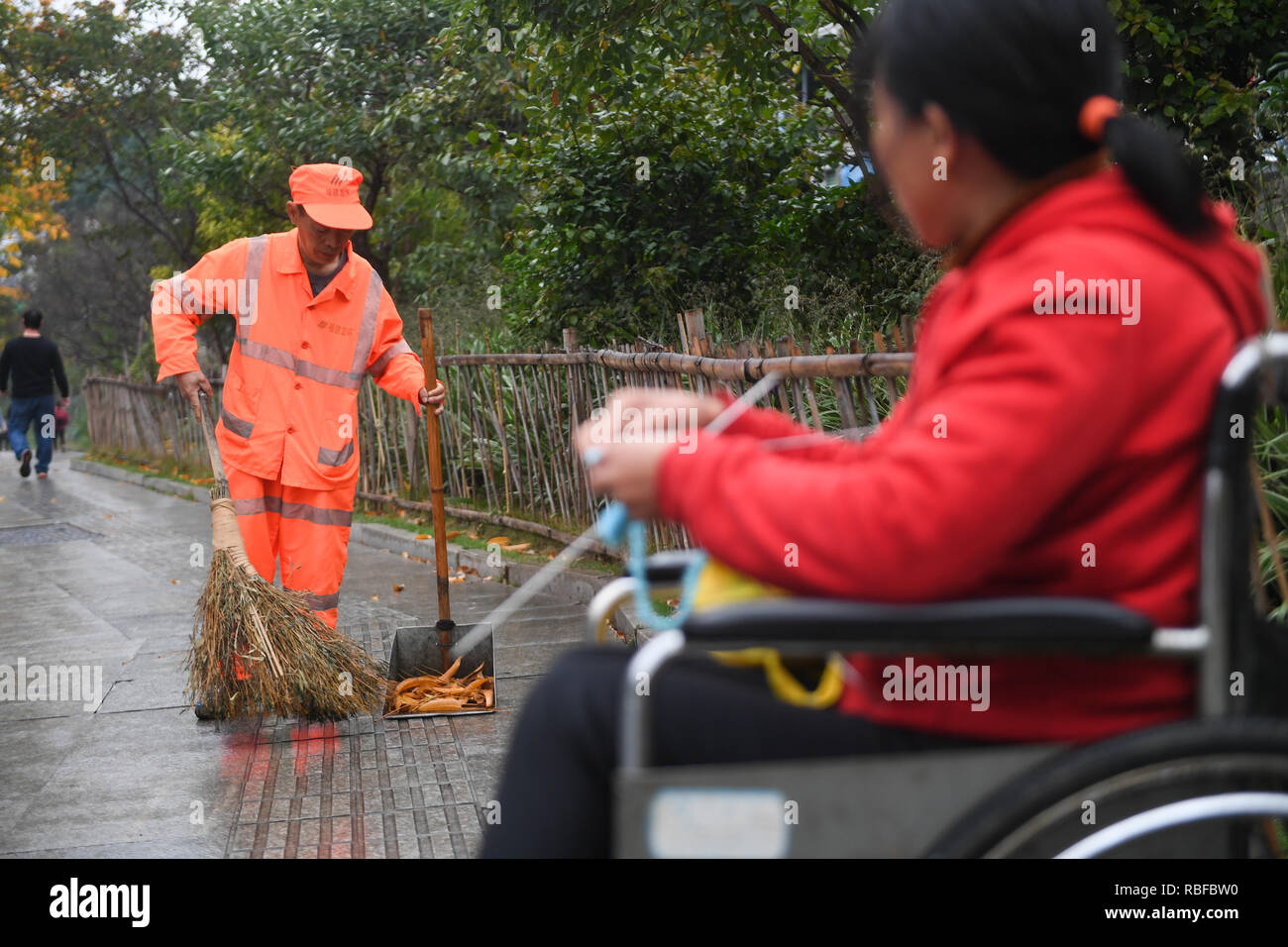 (190110) -- LONGYAN, Jan. 10, 2019 (Xinhua) -- Sanitation worker Dong Jidong cleans the streets accompanied by his handicapped wife Dong Jinxiang in Xinluo District of Longyan City, southeast China's Fujian Province, Jan. 9, 2019. Due to femoral head necrosis disease, Dong Jinxiang has been living on a wheelchair for about a decade. To take care of his handicapped wife, Dong Jidong, who himself has been afflicted with ankylosing spondylitis, gave up his work in a cement plant and chose to clean the streets near their home two years ago just in order to take better care of his wife. Everyday, D - Stock Image