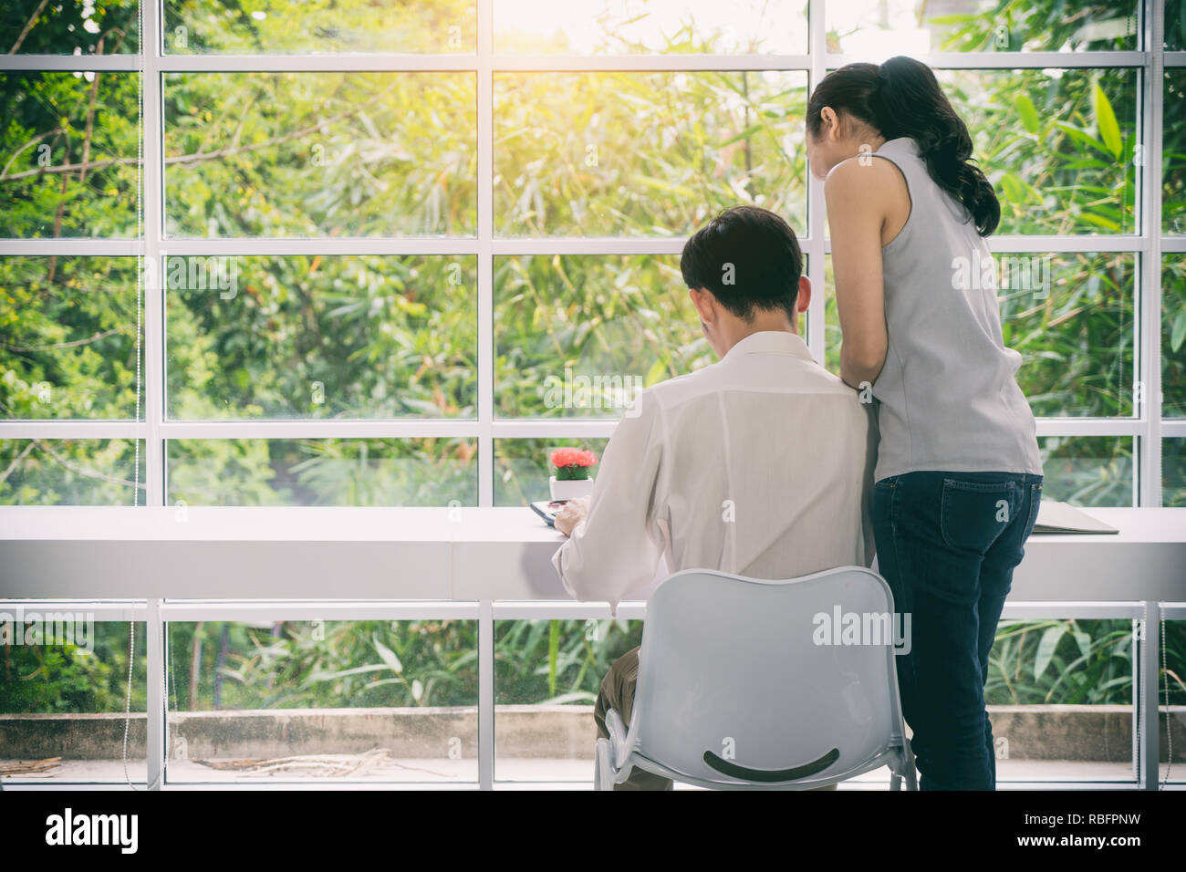 Asian business couple working together on project at modern startup office. Senior business woman suggestion new worker man at desk in office. - Stock Image
