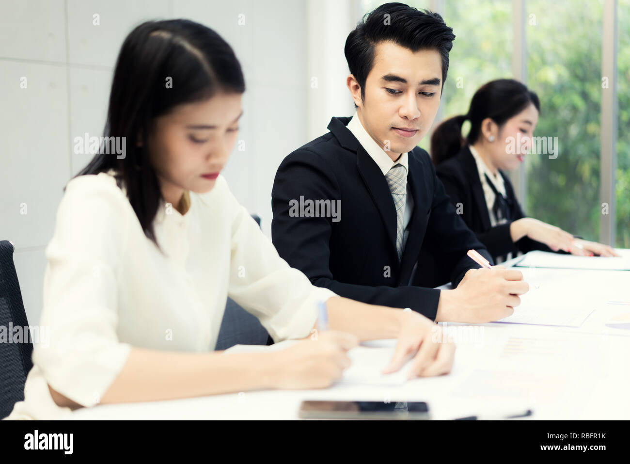 Inquisitive curious businessman with bad manners sneakly looking at report of businesswoman trying to steal idea of competitor, copying work at corpor - Stock Image