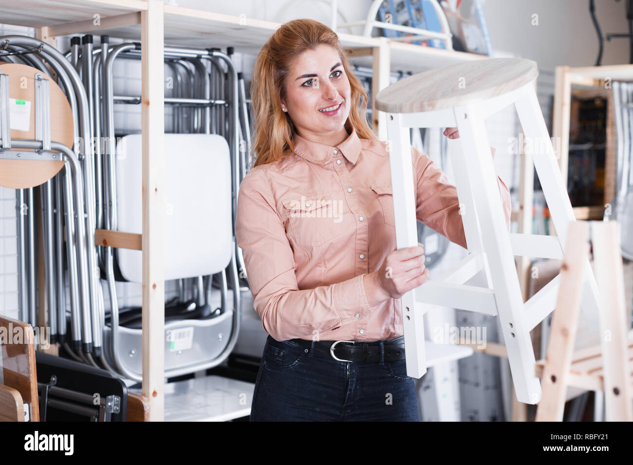 Attractive woman looking for new stylish tabouret for apartment in furniture salon - Stock Image