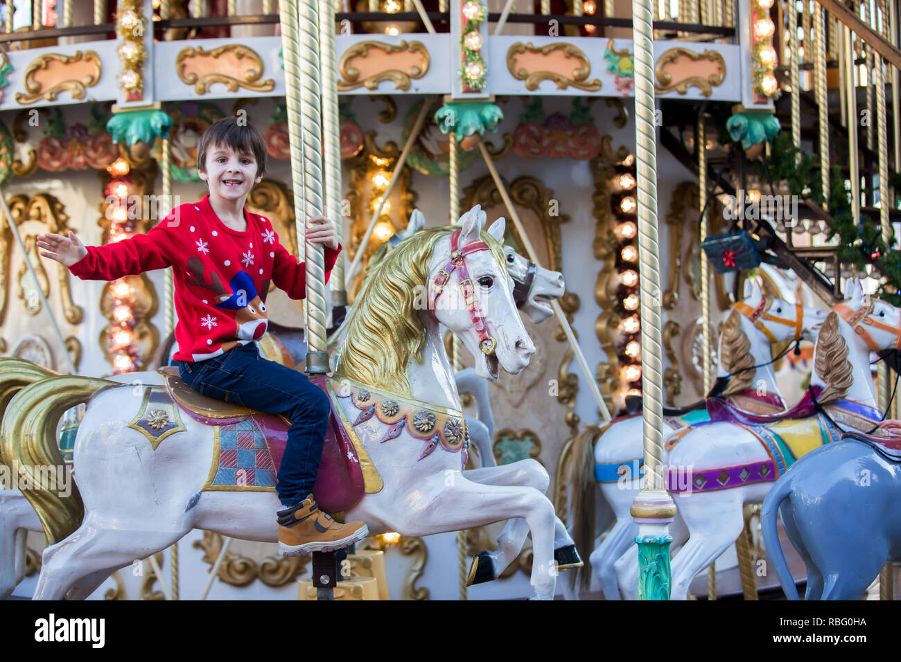 Sweet boys, brothers, riding in a Santa Claus sledge on a merry-go-round, carousel attraction in Europe, active children, wintertime Stock Photo