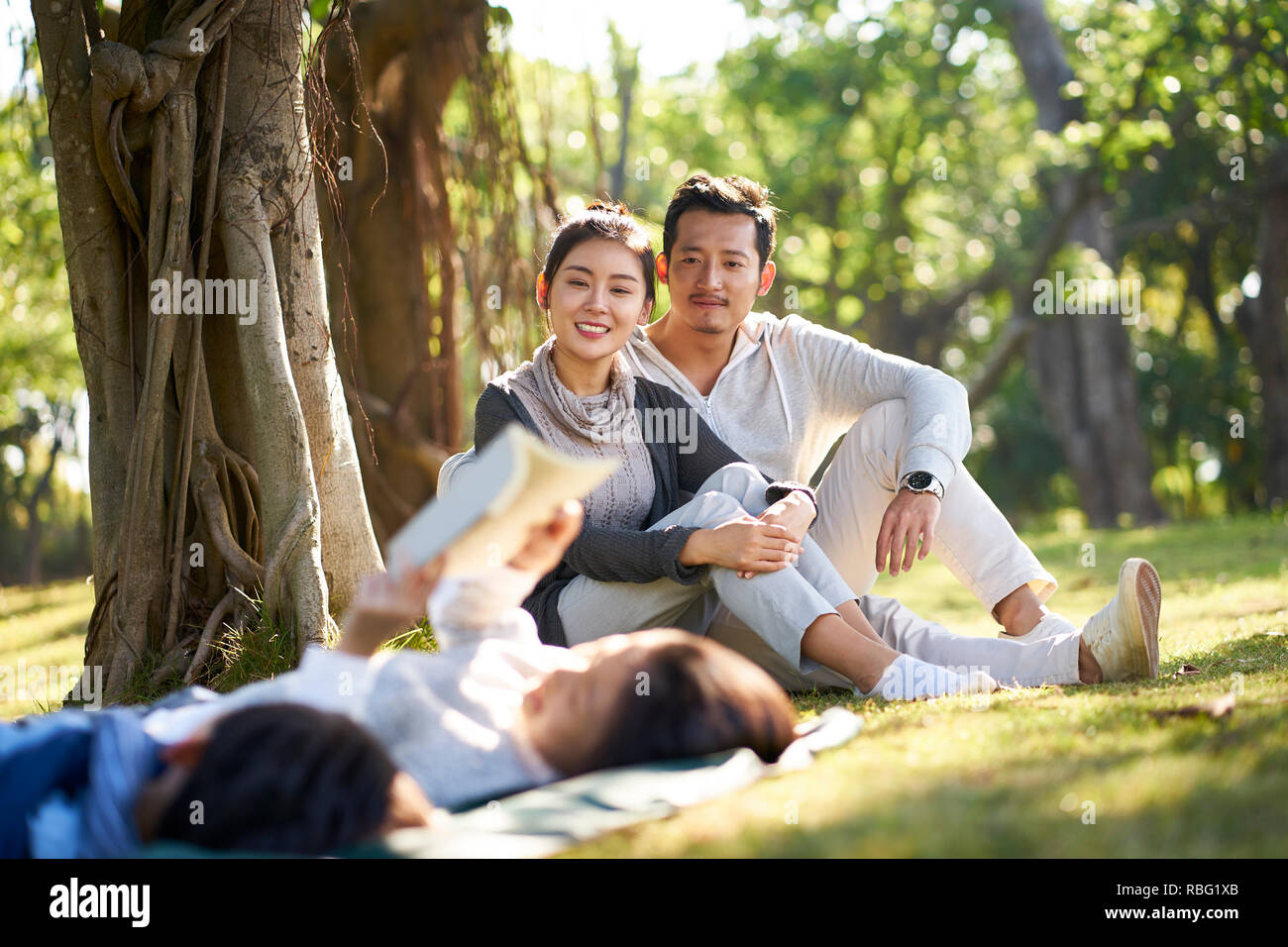 two asian children little boy and girl having fun lying on grass reading a book with parents sitting watching in background. Stock Photo