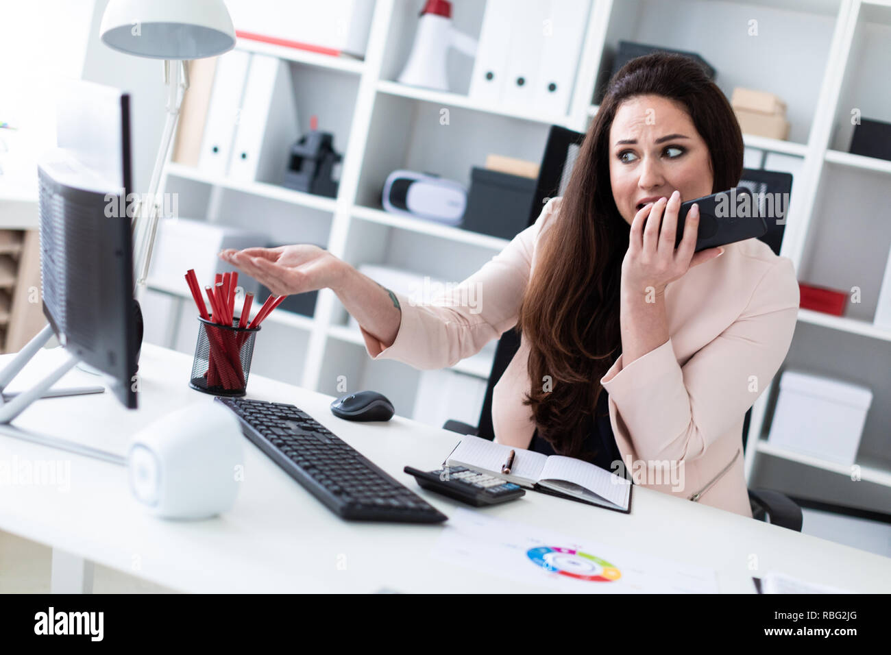 A young girl sitting at a computer old, holding a phone and looking at the monitor. - Stock Image