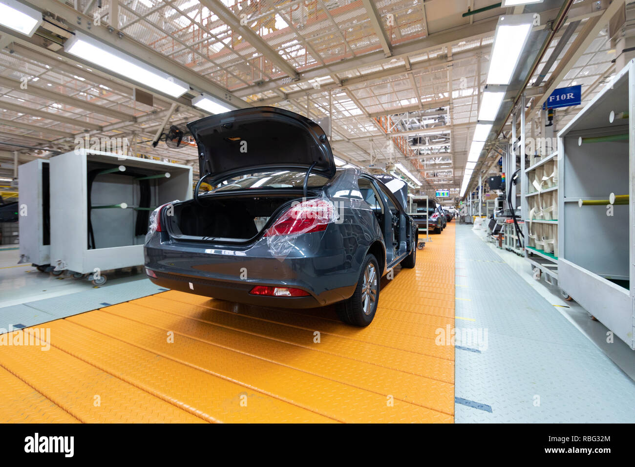 Assembled car is on the Assembly line. Robotic equipment makes the Assembly of the car. Modern car Assembly at the factory Stock Photo