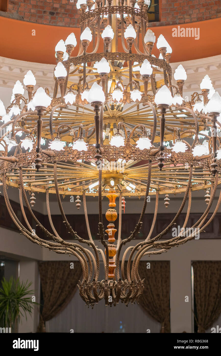 Huge chandelier in the hall. Chandelier on decoarted ceiling of a ballroom. vertical photo Stock Photo