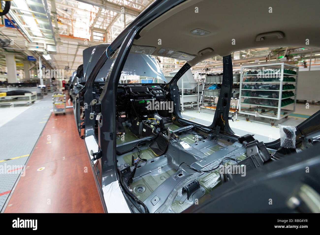 Add details to car body. Robotic equipment makes Assembly of car. Modern car Assembly at factory - Stock Image
