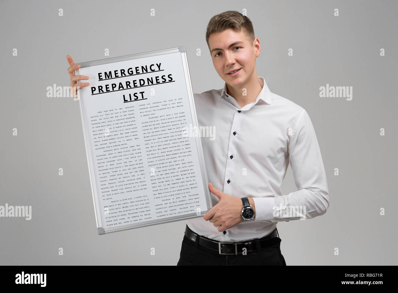 Young man holding a list of Emergency preparedness isolated on a light background - Stock Image