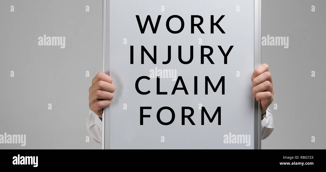 men's hands holding a poster with the inscription form with a claim of injury at work isolated on a light background - Stock Image