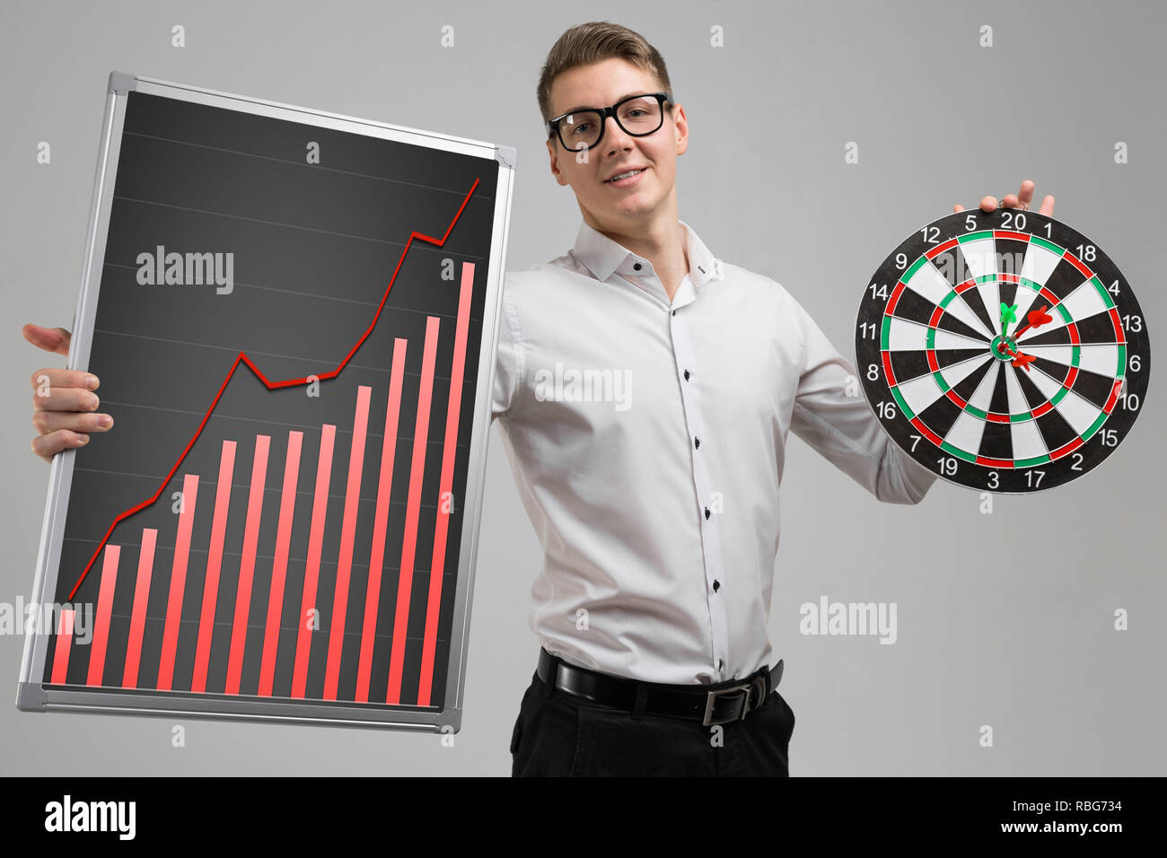 Young man in glasses holding a Board with increasing statistics and Darts isolated on white background - Stock Image