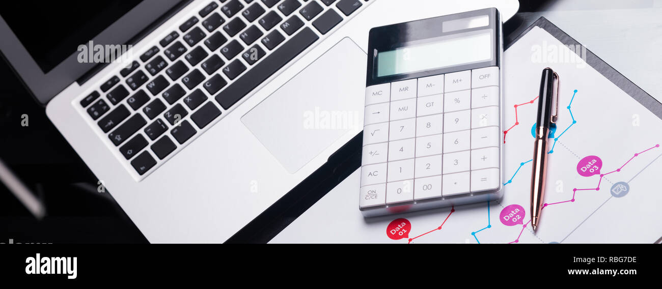 Modern calculator is on a laptop and on a sheet with a graph - Stock Image