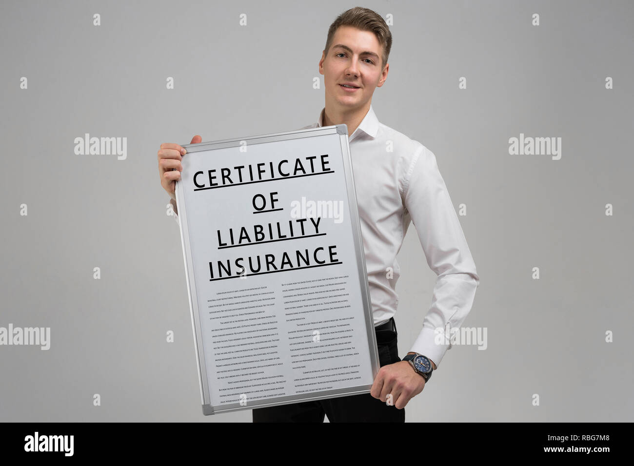 young man holding a certificate of liability insurance isolated on a light background - Stock Image