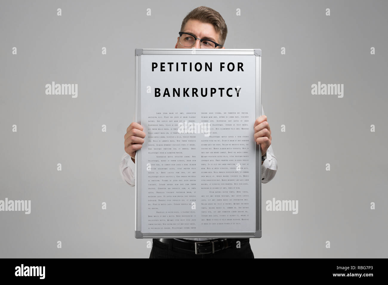 Young man keeps in front of him petition for bankruptcy isolated on light background - Stock Image