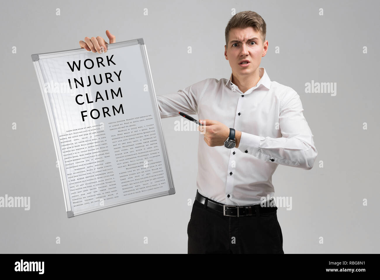 young man holding a form with a claim of injury at work isolated on a light background - Stock Image