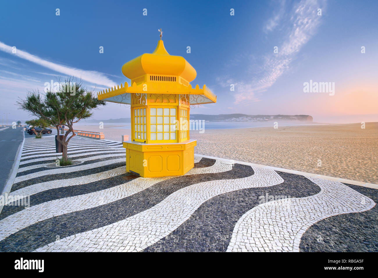 Yellow kiosk on cobble stone  sidewalk with black and white ornament at wide lonely sand beach - Stock Image
