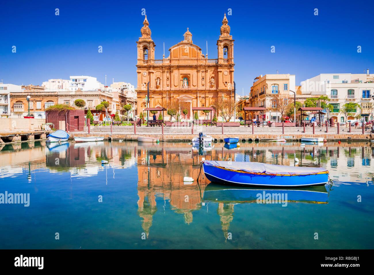 Valletta, Malta. Msida Marina boat and church reflection into water. - Stock Image