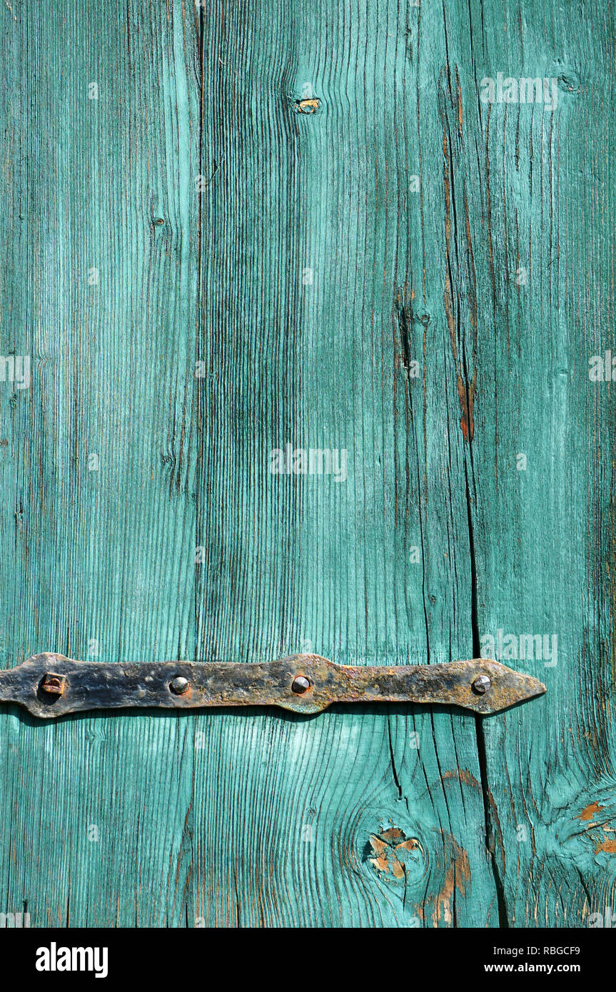 Part of an old weathered green wooden door with rusty metal fittings Stock Photo