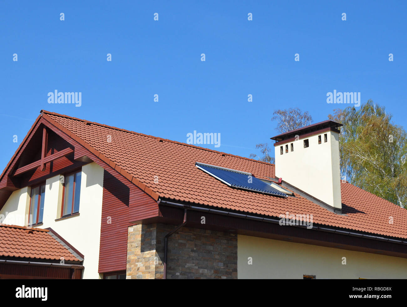 Energy Efficiency New Passive House Building Concept Exterior. Cozy house Roofing with Vacuum Solar Water Panel Heating, Solar Panels, Skylights Outdo - Stock Image