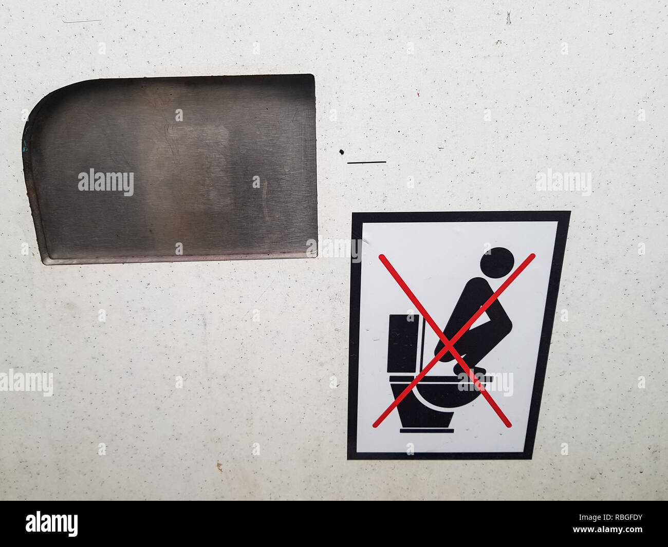 'Don't stand on the toilet seat' sign inside a dirty public toilet '