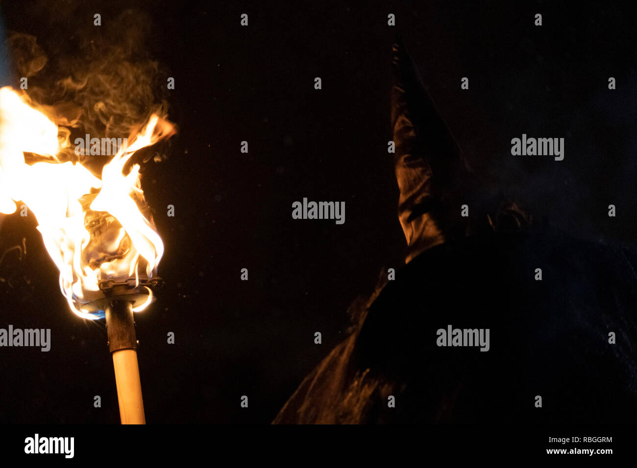 witch in the black holding a flame torch - Stock Image