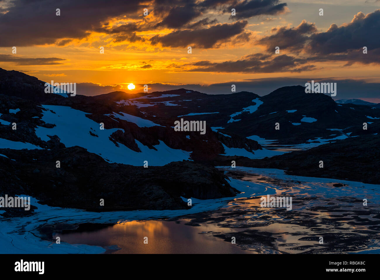 The spring sunset setting the mountain landscape with a melting lake in the valley. Norway, Aurlandsfjellet. - Stock Image