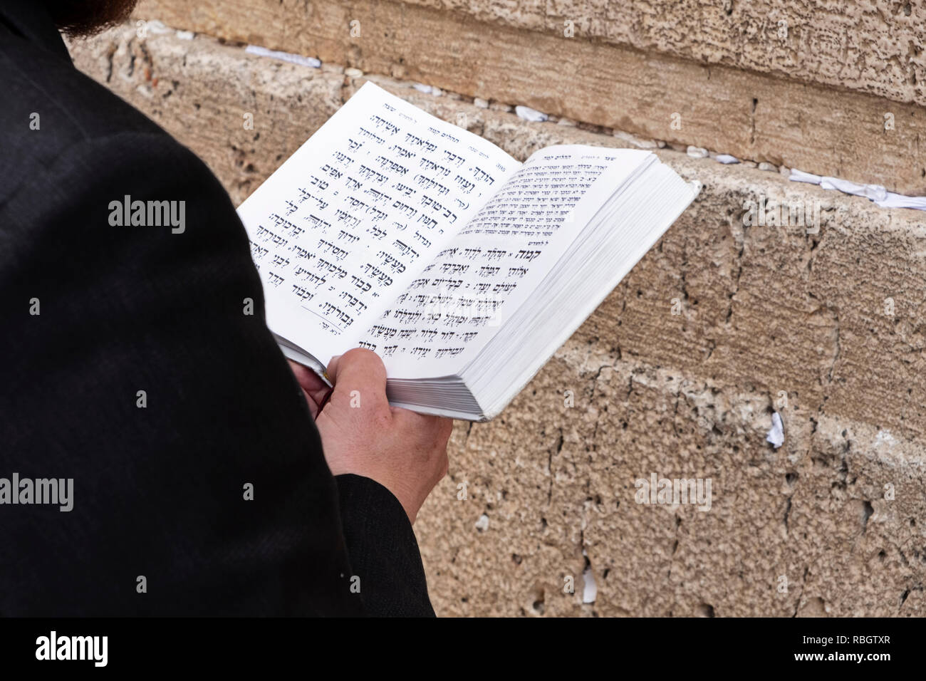 JERUSALEM, ISRAEL - JUNE 14, 2018: A man reading the torah and praying at the Wailing Wall in the Old City of Jerusalem in Israel. - Stock Image