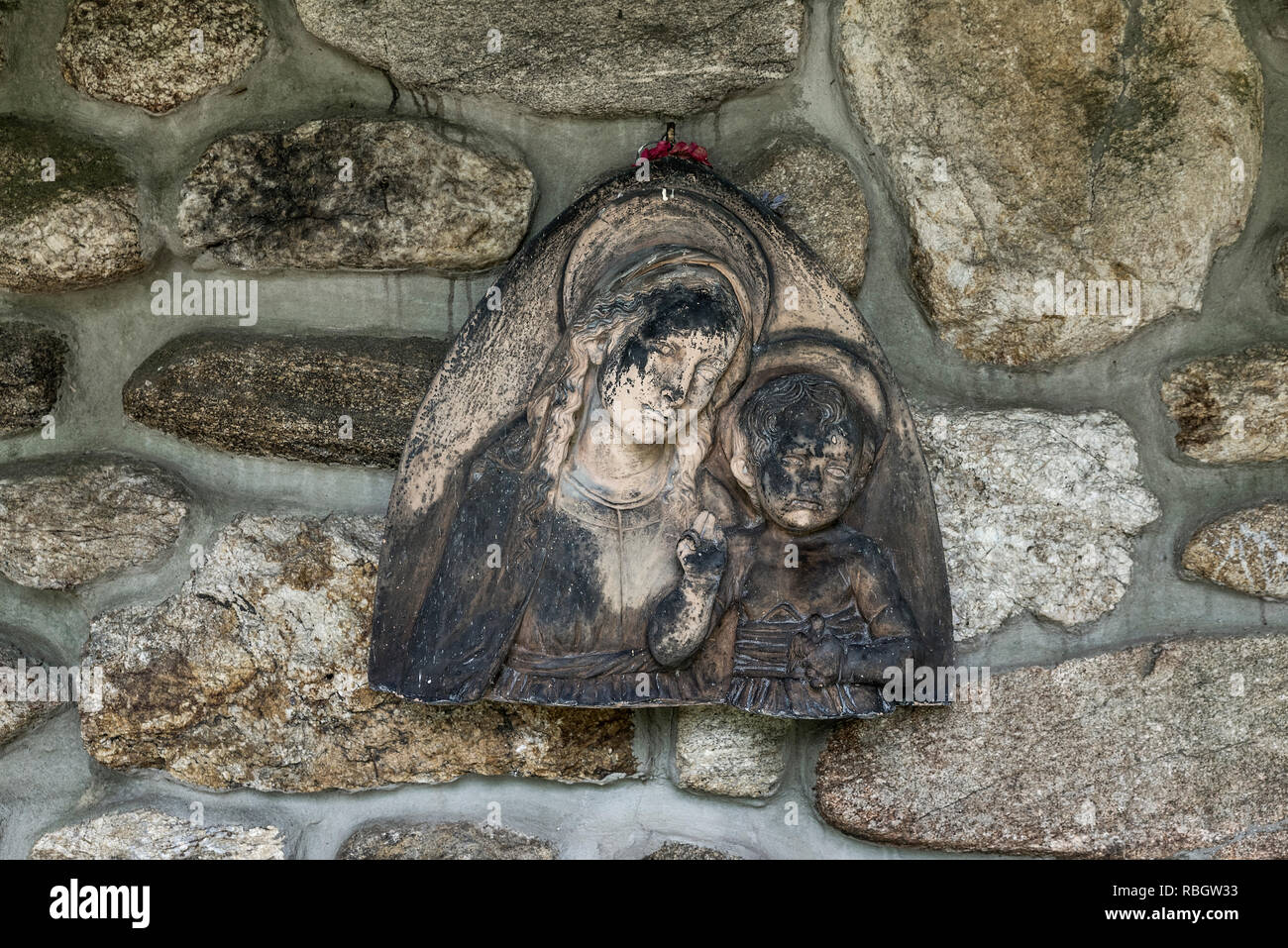 Madonna and child carving against the fieldstone wall of a monastic church, St Joesph Trappist Abbey, Spencer, Massachusetts, USA. - Stock Image